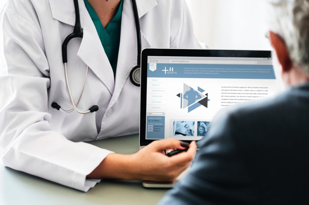 Doctor showing patient results on laptop